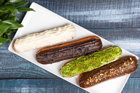 Tasty chocolate eclair cakes with leaves on the blue background, top view 免版税图像