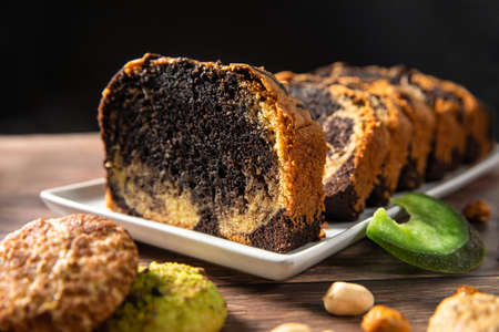 Sweet swiss roll roulette with caramel and cream and milk chocolate shards over it 免版税图像