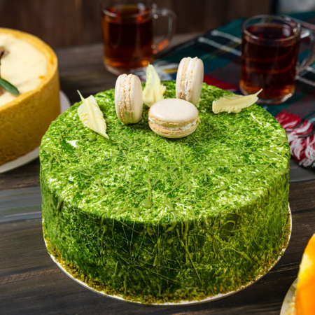 Different beautiful macaron cake on the wooden table with tea