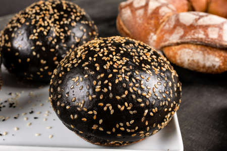 Fresh dark, black burger bread close up 免版税图像