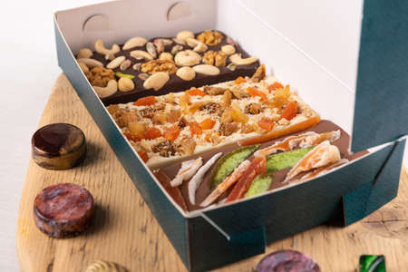 Luxury chocolate pieces, rose, pomegranate, nuts in the box 免版税图像