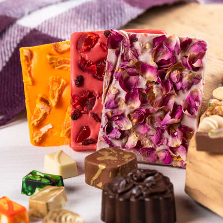Luxury chocolate pieces, rose, pomegranate close up 免版税图像