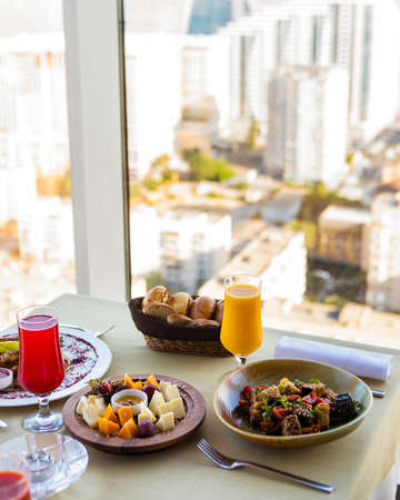 Tasty meals, cheese mix, fruit juice on the restaurant table 免版税图像