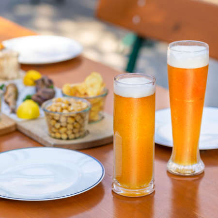 Beer mugs, glasses with snacks on the table