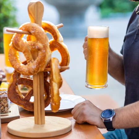 Man holding beer mug with pretzel on the table 스톡 콘텐츠