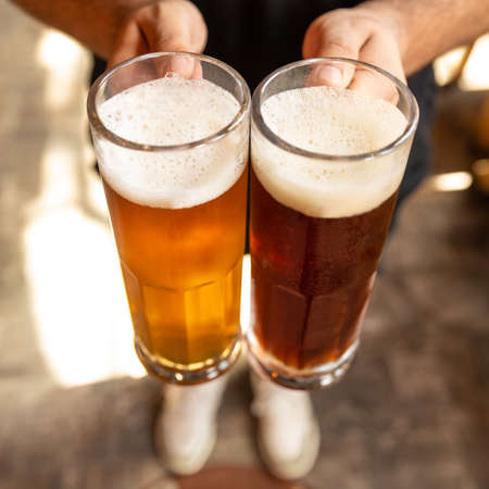 Man holding white and black beer side by side