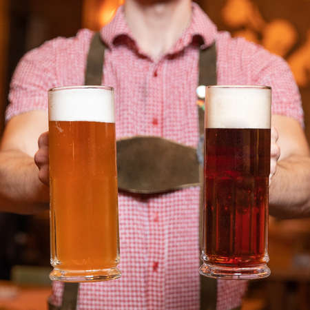 Man holding white and black, dark beer glasses side by side