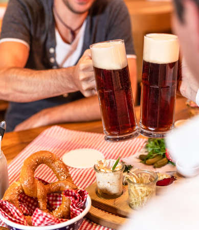 Clinking dark, black beer mugs close up, snacks on the table
