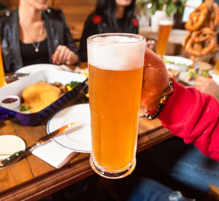 Man holding beer mug, friends, restaurant 스톡 콘텐츠