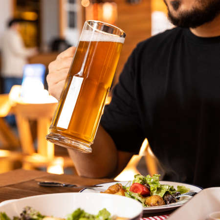 Man drinking beer with salad