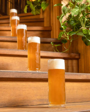 Beer drink glasses, mugs on the wooden stairs 스톡 콘텐츠