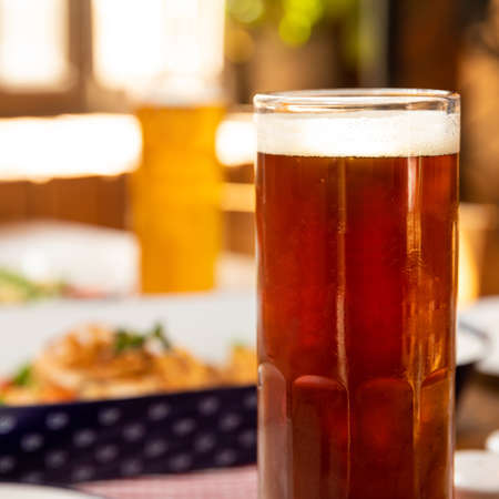 Dark beer glass with dish close up