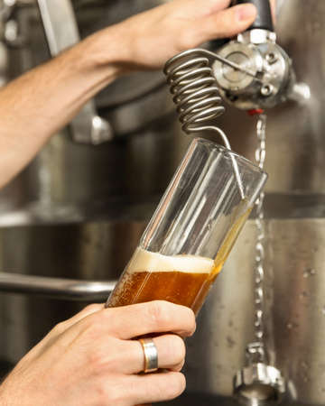 Man pouring, filling beer glass, mug from barrel