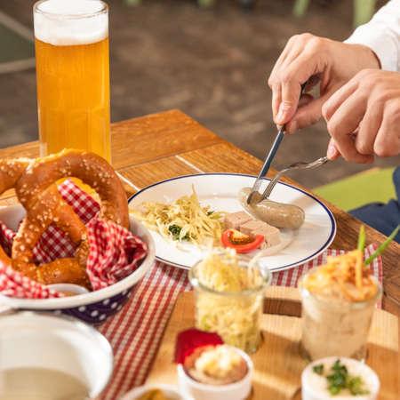 Man cutting tasty German sausage, beer