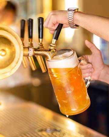 Man pouring, filling beer glass, mug