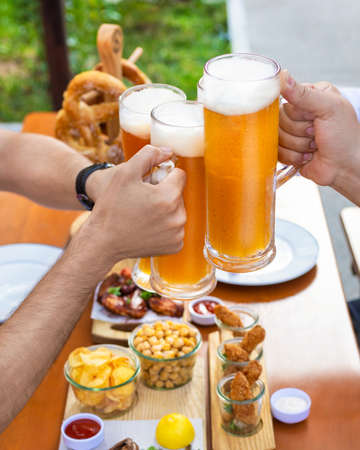 Clinking beer mugs outside, snacks on the table