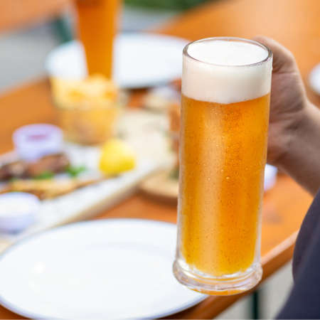 Man holding beer mug with snacks on the table