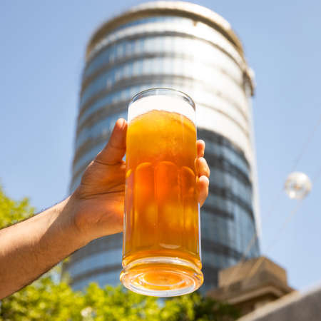 Man holding beer mug, glass with building background