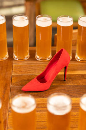 A lot of beer drink glasses, mugs on the table with red women shoes