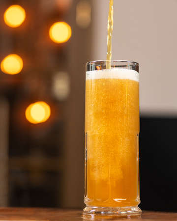 Beer pouring, filling to the mug, glass with bokeh background