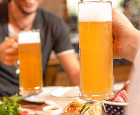 Two man holding beer drink mug, snacks on the table