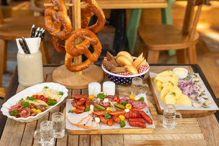 Sausage with cheese and fermented cucumbers, pretzel snacks with vodka on the table 스톡 콘텐츠
