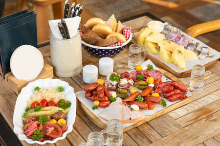 Sausage with cheese and fermented cucumbers, snacks with vodka on the table 스톡 콘텐츠