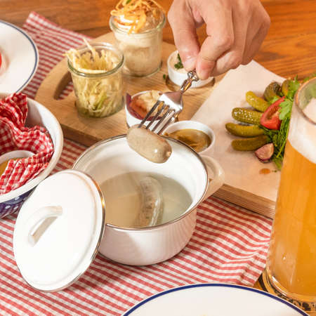 Man taking out hot German sausage with beer 스톡 콘텐츠