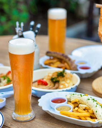 Beer mugs with sausage, meat meal, pretzel, sauce on the table