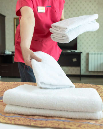Hotel room service, woman puts a towel on the bed Banque d'images - 151145820