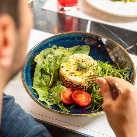 Man eating tasty salad top view