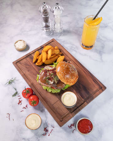 Tasty burger with fried potato, juice on wooden plate