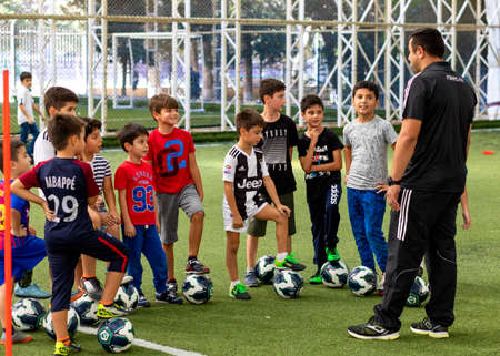 Trainer with young football, soccer players at the stadium
