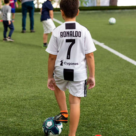Young boy standing with soccer ball at the stadium Редакционное