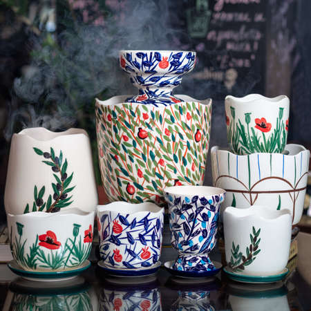A lot of hand painted pots on the table