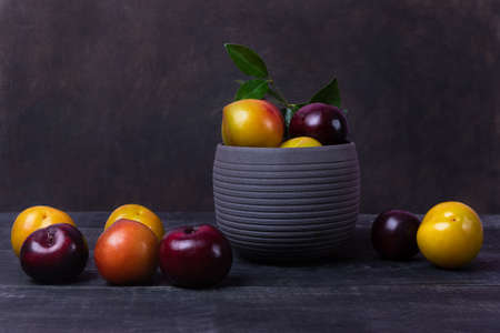 Colorful plums fruit in pot and plate on the black background isolated