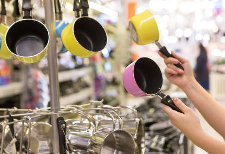 Woman holding colorful small pans at the store 免版税图像 - 156103563