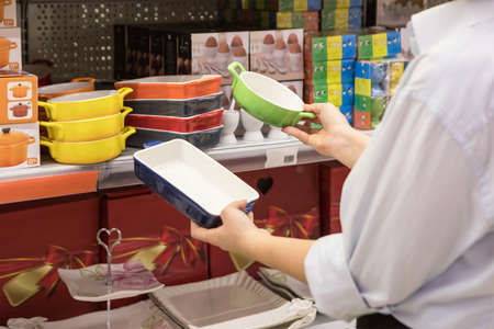 Woman holding a colorful kitchen plates at the store 免版税图像 - 156103628