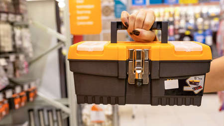 Woman holding orange heavy duty plastic tool box at the store 免版税图像 - 156103629