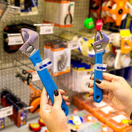 Woman holding a blue adjustable wrench at the store