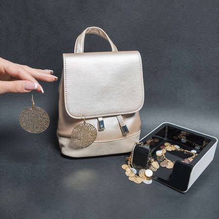 Holding a jewelry earrings with a woman bag isolated