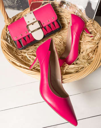 Red high-heeled shoe with a handbag in the basket 免版税图像 - 156135338