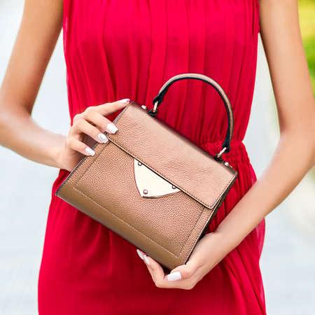 Dressed in red woman holding a luxury handbag 免版税图像 - 156135155
