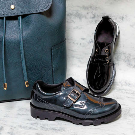 Black shiny boy male shoes with a blue backpack isolated 免版税图像 - 156135033