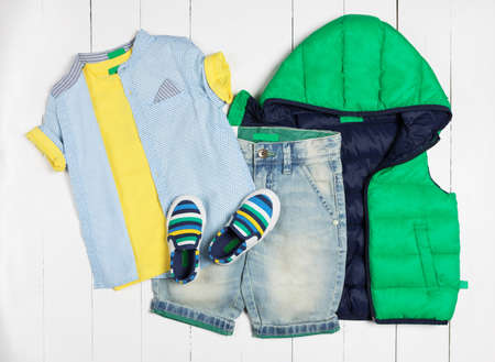 Men's casual outfits for man clothing set with yellow t-shirt, shoes, jeans shorts isolated on a white background, top view 免版税图像 - 156134904