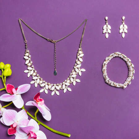 Elegant gold necklace bracelet and earrings with diamonds on purple background 免版税图像 - 156279499
