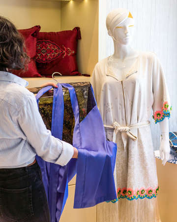 Woman holding a new robe at the store