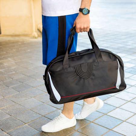 Young man holding a black sport bag close up 免版税图像 - 156253750