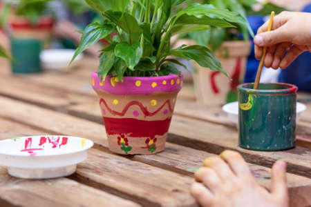 Children are painting potted plants made of pottery close up 免版税图像