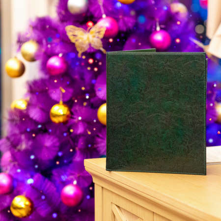 Restaurant menu book with purple Christmas tree close up